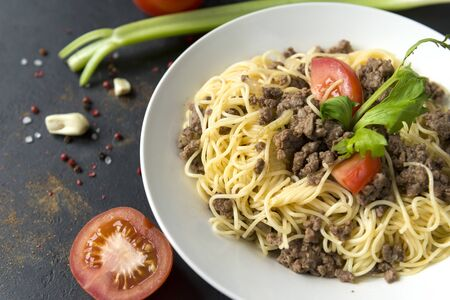 plate of pasta with meat sauce and tomato, celery on a dark background