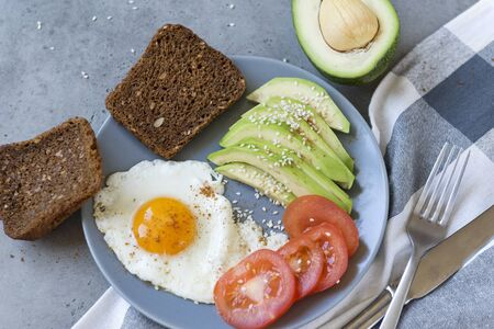 fried eggs with avocado slices and tomato on a gray plate, whole grain bread, fork, knife, towel on a gray background, top view,