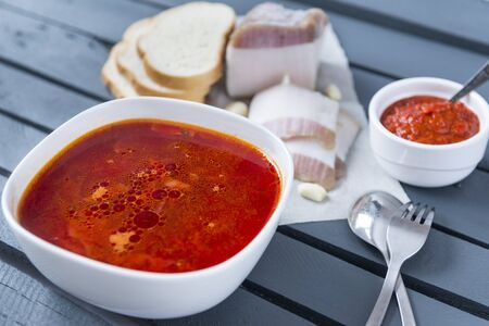 soup, plate of red Ukrainian borscht with bacon and ketchup on a gray wooden background, spoon