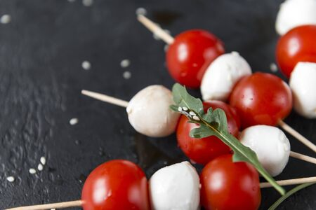 mozzarella balls with cherry tomatoes on skewers, arugula leaf with sesame seeds, canapes on a black background, cheese with vegetables