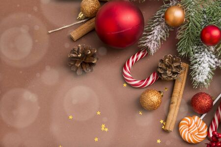 fir branch, fir cones, gold and red Christmas balls, cinnamon sticks, stars,  Lollipop on a brown background,