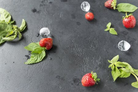 fresh mint, strawberry with ice pieces on black background