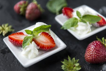 berries, strawberries with cream and mint on a black background ,
