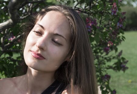 portrait of a beautiful girl on the background of a lilac Bush, a young woman in nature Reklamní fotografie