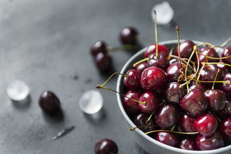 cherry berries,  plate of cherries on a black background, pieces of ice,  many  berries
