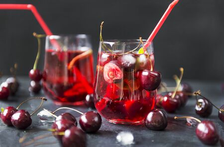 lemonade with cherries in a glass on a black background