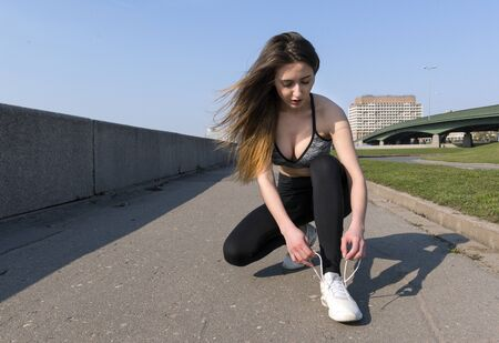 slim girl with long hair in sports clothes tying shoelaces in sneakers, city Reklamní fotografie