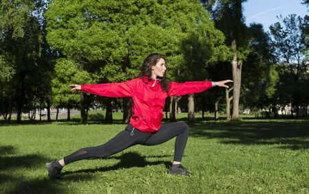 girl stands in the pose of a warrior, girl in a red jacket engaged in sports, yoga in the Park in a clearing among the trees,
