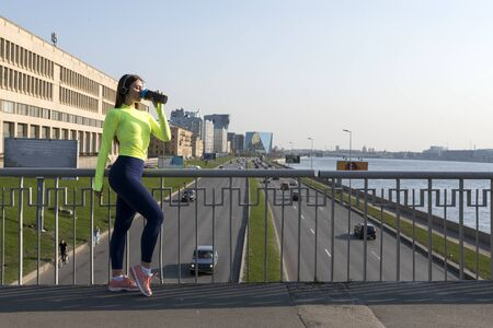 girl in sports clothes drinking water on the bridge over the road with cars in the city, the Neva river embankment, St. Petersburg