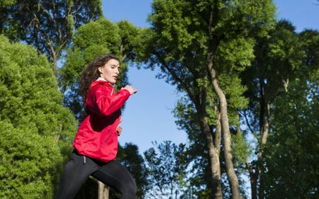 runner, girl in a red jacket runs on a background of timbers of trees and blue sky,  runner