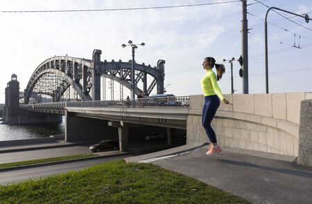 slender girl in sports clothes jumping rope on the river embankment on the background of the bridge, St. Petersburg, outdoor fitness, sports in the city