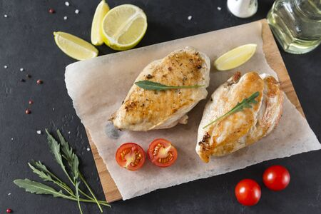 2 pieces fried chicken fillet on cutting Board ,cherry tomatoes, arugula, lemon on dark background