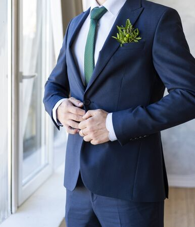 man in a blue suit with a green tie and a white shirt with a boutonniere in front of the window,  groom
