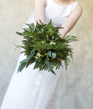 bride in a white dress holding a bouquet of green flowers