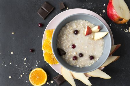 oatmeal with pieces of pear, cranberries, orange and chocolate on a black background, a plate of porridge