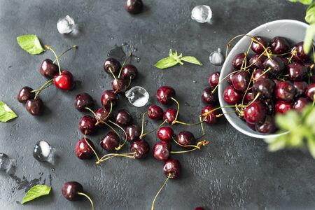 plate scattered with fresh cherries, mint and ice cubes on dark background