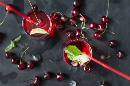 2 cups with cherry juice and fresh cherry on a dark background, top view, straws, drink