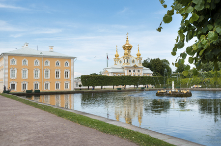 pond with a fountain in Peterhof,  Russian Orthodox Cathedral with Golden domes,  building of the Palace, Park,, Sunny day Redakční