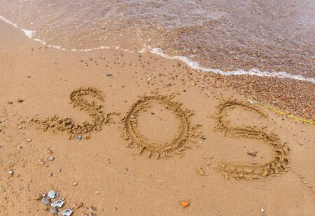 inscription SOS on the sand with sea water, beach