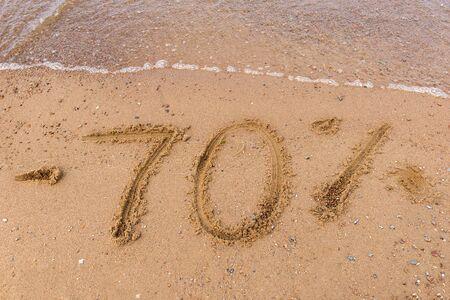 inscription on the sand minus 70 %, discounts ,sea water, beach