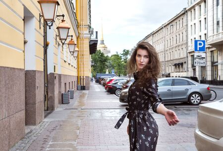 1 white beautiful young woman in the city on the street on the background of buildings in classic style, St. Petersburg Imagens