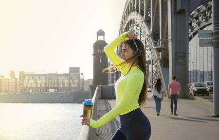 1 white sports girl with long hair in a green sports top stands on the bridge at sunset, a girl with a bottle of water in her hands on the bridge, Фото со стока