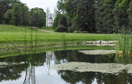 Catholic chapel among the trees near the pond with reeds, country landscape