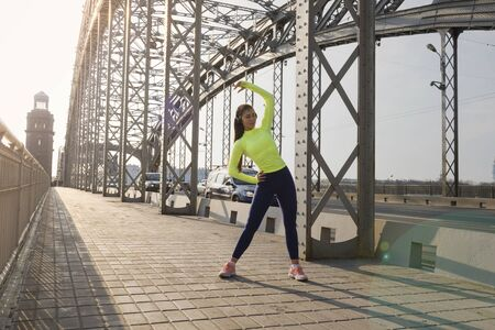 1 white sports girl in sports clothes doing fitness on a metal bridge in the city at sunset