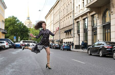 slender young woman with long hair in a long brown dress and shoes on St. Petersburg street in summer, buildings, parked cars, Admiralty spire