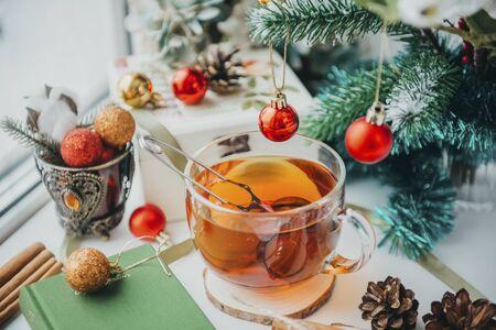 1 mug of hot black tea near the window, spruce branch with red ball, cones, Christmas decor, Christmas spirit ,
