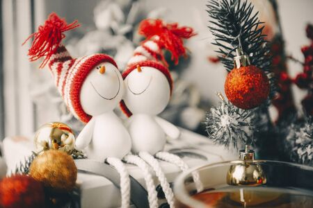 2 toy snowmen in striped hats near a spruce branch with a red ball, Christmas decor