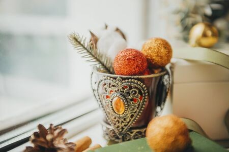 brown glass vase with orange stones with a sprig of spruce, cotton, red and gold balls near the window, Christmas spirit, decor