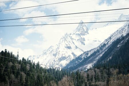 mountain peaks covered with snow in winter, Caucasus, spruce forest at the foot of the mountains, mountain winter landscape