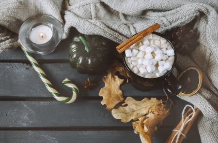 mug of hot coffee, chocolate with lots of marshmallows and candy, cinnamon, small green pumpkin, candle , dry autumn leaves, candy, cone, close with a knitted sweater on a black background, autumn hot drink
