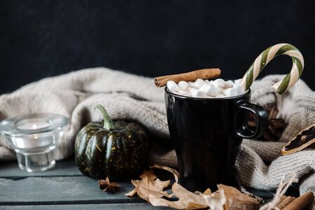mug of hot coffee, chocolate with lots of marshmallows and candy, cinnamon, small green pumpkin, candle , dry autumn leaves next to a knitted sweater on a black background
