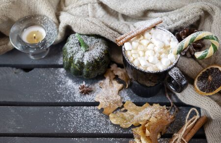 mug of hot coffee, chocolate with lots of marshmallows and candy, cinnamon, small green pumpkin, candle , and dry autumn leaves next to a knitted sweater on a gray wooden background,