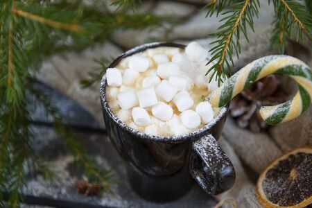 mug of hot coffee, chocolate with lots of marshmallows and Lollipop,   background of green fir branches, winter hot drink,  Christmas spirit