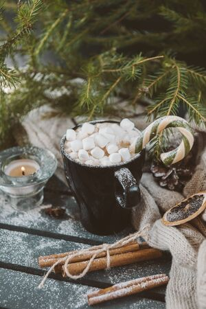 mug of hot coffee, chocolate with lots of marshmallows and candy, the cinnamon, the candle next to the knitted fabric on a background of green fir branches, winter hot drink, the Christmas spirit 版權商用圖片