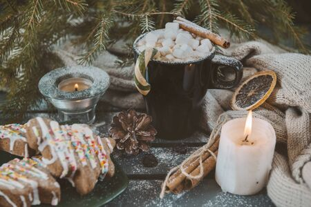 1 mug with hot chocolate and marshmallows, cinnamon stick and Lollipop, candle, spruce branch, cone, cookies, knitted fabric  on a dark background, 版權商用圖片