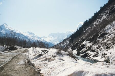 road among the Caucasus mountains in winter, summits , peaks and slopes are covered with snow on a Sunny day