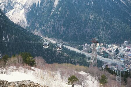 cable car in the Caucasus mountains, town in the valley at the foot of the mountains mountain slopes in winter