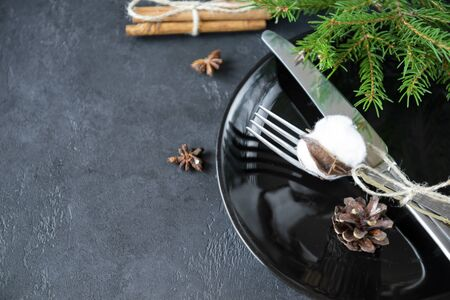 fork with knife and cotton branch on a black plate against a spruce branch on a black background, cinnamon sticks, cone Stock fotó