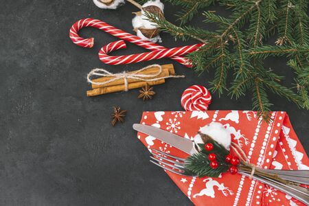 spruce branches, cinnamon, cotton branch, candy,   fork, knife. Christmas decor on a black background, red napkin with Cutlery, top view, Stock fotó