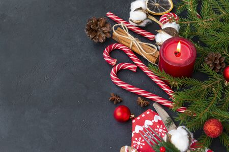 fir branches, candle, cinnamon, twig, cotton branch , fir cones, red balls, Christmas decor on a black background, red napkin with Cutlery,  top view