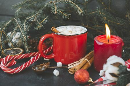 1 mug of hot Christmas drink with marshmallows, candle, lollipops, fir branch, spoon, cotton branch, cotton, Stok Fotoğraf