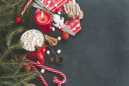 1 red mug of hot Christmas drink with marshmallows, cinnamon, candle, lollipops, spoon, fir branch, napkin, cookie, fork, knife, cone ,  hot chocolate, coffee, spoon,