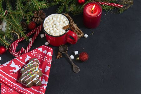 1 red mug of hot Christmas drink with marshmallows,  candle, lollipops,  cinnamon,, spoon, fir branch, hot chocolate, coffee, spoon, napkin, cookies ,