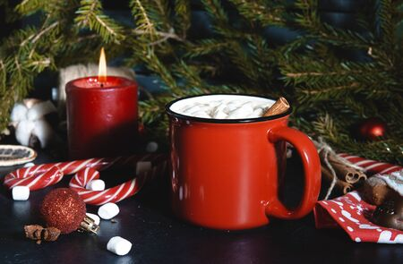 1 red mug of hot Christmas drink with marshmallows, candle, lollipops, fir branch, hot chocolate, coffee Stok Fotoğraf
