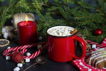 1 red mug of hot Christmas drink with marshmallows, candle, lollipops, spoon, fir branch, hot chocolate, coffee Stok Fotoğraf