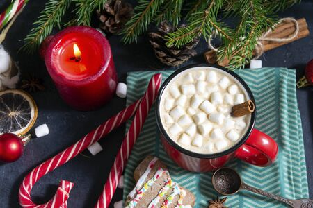 1 red mug with hot chocolate and marshmallows and cinnamon stick, fir branches,  candle, lollipops, napkin, red balls, winter, Christmas hot drink